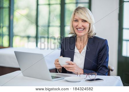 Portrait of businesswoman holding coffee cup in a restaurant