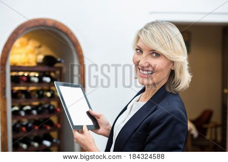 Portrait of businesswoman holding digital tablet in a restaurant
