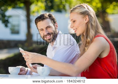 Happy couple using mobile phone in a restaurant