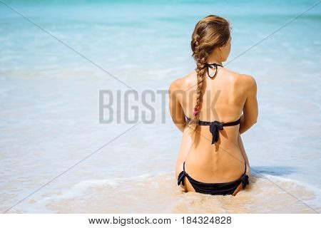Outdoor summer portrait of young elegant pretty fit woman sitting backwards and looking on sea at tropical beach. Sports girl in bikini enjoy nature paradise at wonderful summer vacation in Thailand.