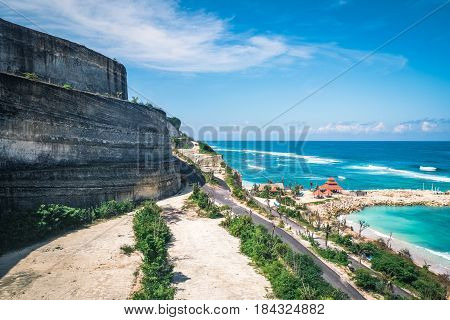 Scenic landscape of high cliff on tropical white sand beach in Bali island. Indonesia tropical nature outdoor landscape with scenic sea water and white foam waves from above
