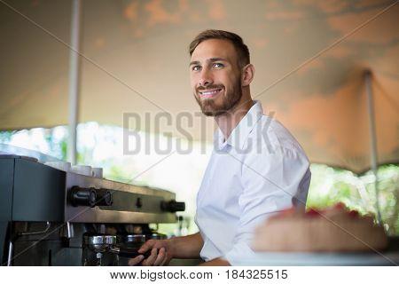 Smiling waiter preparing espresso at restaurant