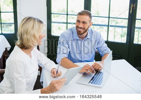 Smiling executives interacting with each other in a restaurant