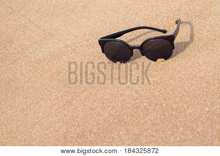 one sunglasses of black color are located separately a closeup on the sandy coast and a blank space