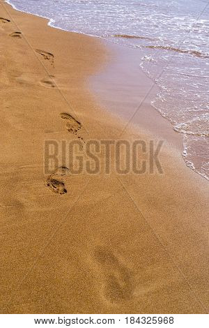 natural background and footprint of human legs on the sandy coast with water of sea waves