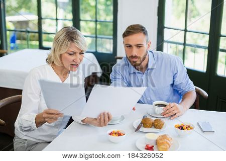 Executives discussing over document in a restaurant