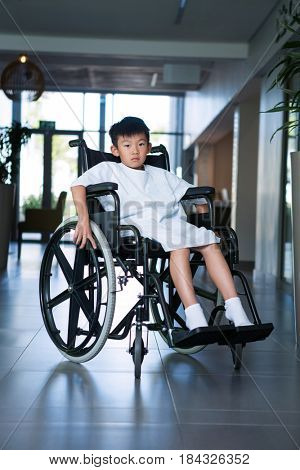 Disabled boy patient on wheelchair in hospital corridor at hospital