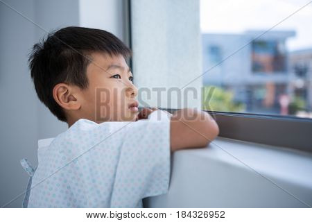Tensed boy patient looking out from the window at hospital