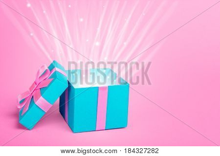 Gift box with a rays of the sun or the light shine from the gift. Box of peppermints and a pink background