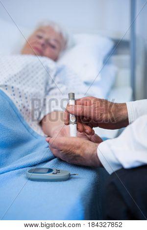 Doctor testing diabetes of senior patient insulin pen in hospital
