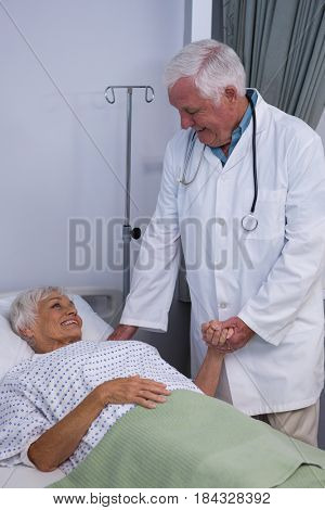 Doctor consoling senior patient in ward at hospital
