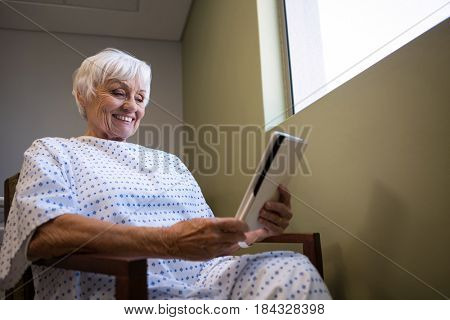 Senior patient holding digital tablet in hospital