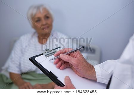 Doctor discussing medical report with senior patient in hospital