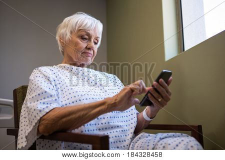 Senior woman using mobile phone in hospital