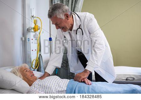 Doctor examining senior patient in ward at hospital