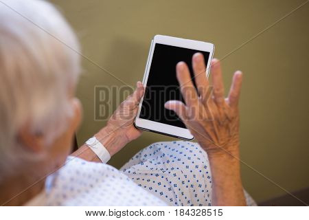 Senior patient using digital tablet to video chat in hospital