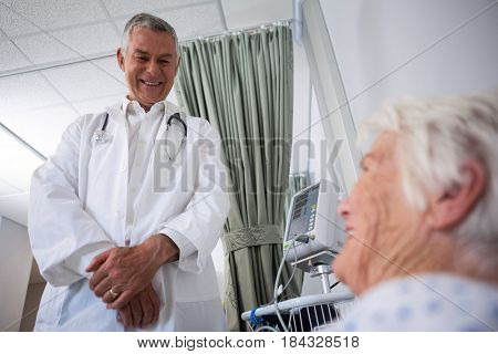 Doctor interacting with senior patient in ward at hospital