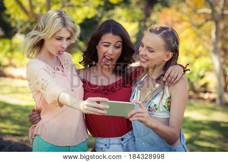 Smiling friends taking selfie with mobile phone in park on a sunny day