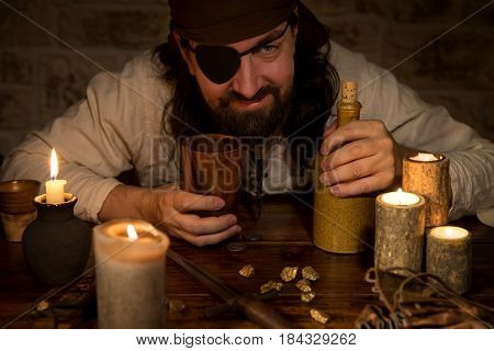 a pirate with rum and a lots of candles and goldnuggets concept medieval and Themeparty