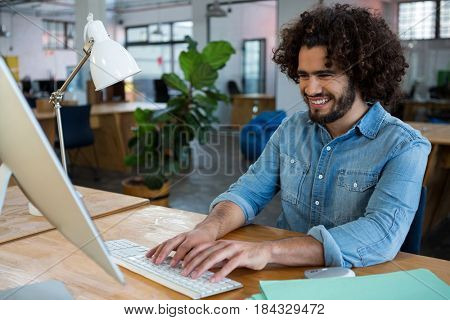Happy male graphic designer working at desk in creative office