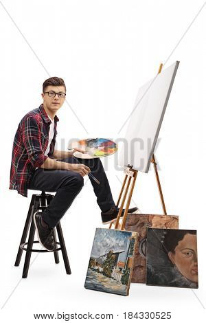 Teenage painter sitting in front of a blank canvas and looking at the camera isolated on white background