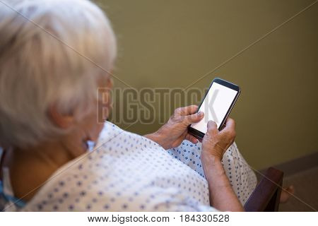 Senior patient using mobile phone in hospital