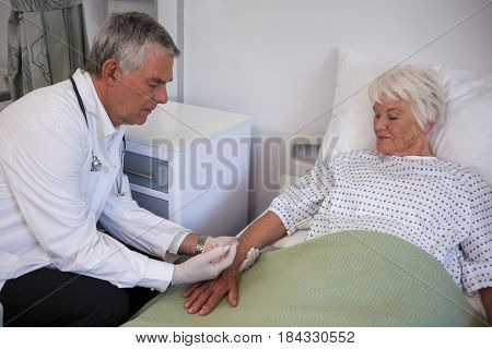 Doctor giving injection to senior patient in hospital