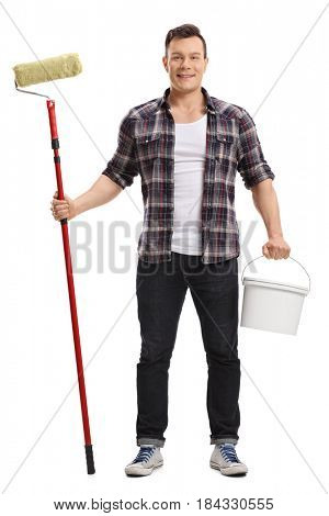 Full length portrait of a young man holding a paint roller and a color bucket isolated on white background