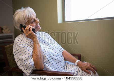 Senior patient talking on mobile phone in hospital