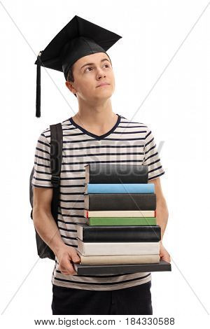Teenage student with a stack of books and a graduation hat daydreaming isolated on white background