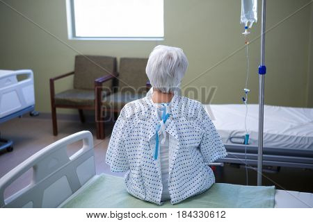 Rear-view of senior patient sitting on bed in hospital