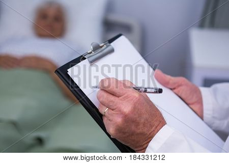 Doctor writing on clipboard in hospital