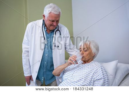 Senior patient drinking a glass of water in hospital