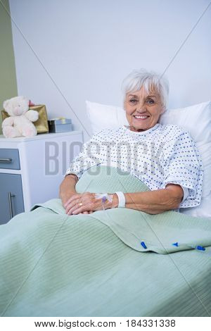 Portrait of smiling senior patient on bed in hospital