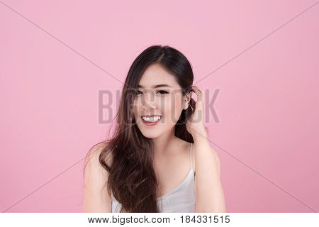 Long hair asian young beautiful woman smile and touch her face isolated over pink background. natural makeup SPA therapy skincare cosmetology and plastic surgery concept
