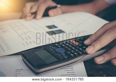 Businessman calculate cost and expenses using laptop for search data result.