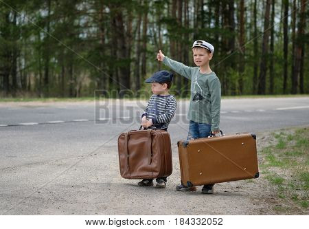 Two boys of European appearance with suitcases on the road