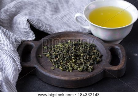A Cup Of Hot Green Tea On A Dark Background. Hot Drink Of Green Tea In A Porcelain Cup, Tea Leaves