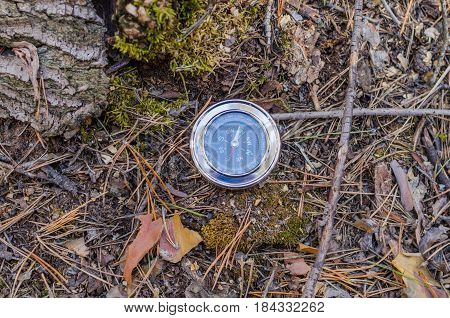The compass lies in the woods on the old moss