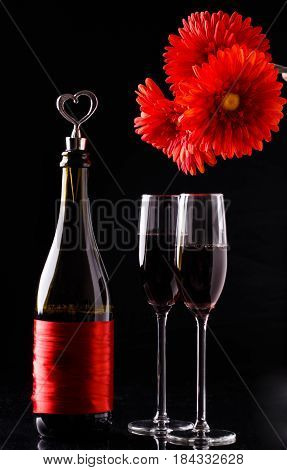 Red flowers, bottle of wine, glasses on black background