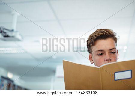Schoolboy reading book in library at school