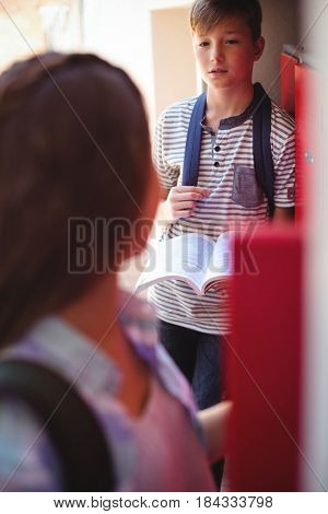 Students interacting with each other in locker room at school
