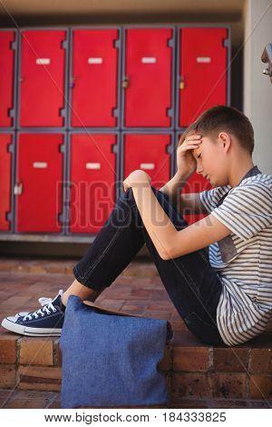 Sad schoolboy sitting on staircase at school