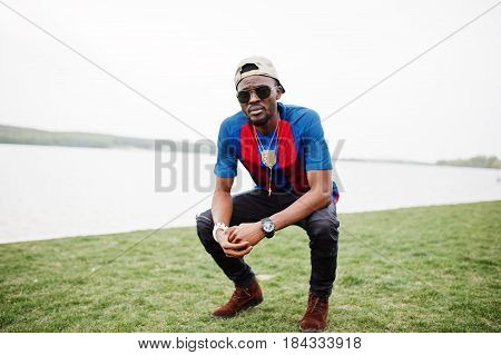 Stylish African American Boy Sat Wear At Cap, Football T-shirt And Sunglasses. Black Sports Man Port