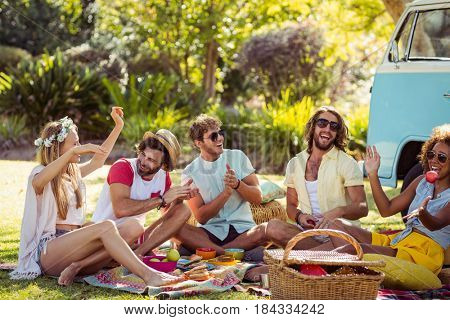 Group of friends having fun together near campervan in park