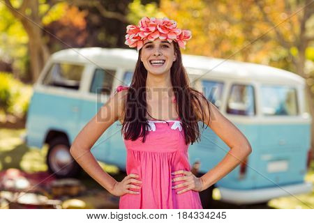 Portrait of happy woman standing with hands on hip in park
