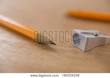 Close-up of yellow pencil with sharpener on wooden background