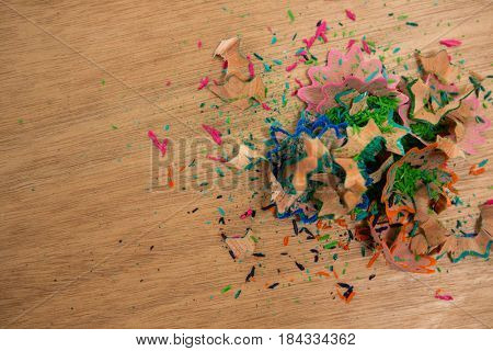 Close-up of colored pencil shavings on wooden background