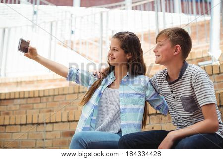 Students taking a selfie on mobile phone in campus at school