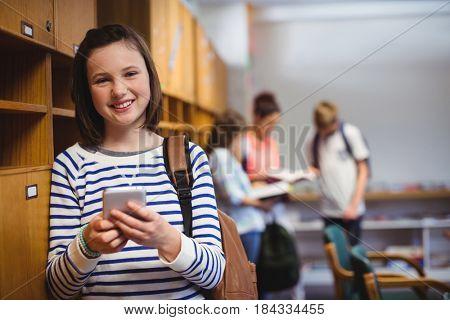 Portrait of happy schoolgirl holding mobile phone in locker room at school